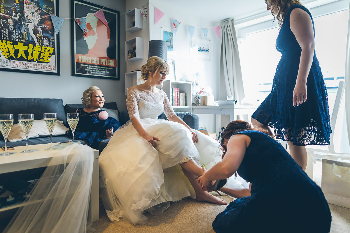 Bride having shoes put on by bridesmaid