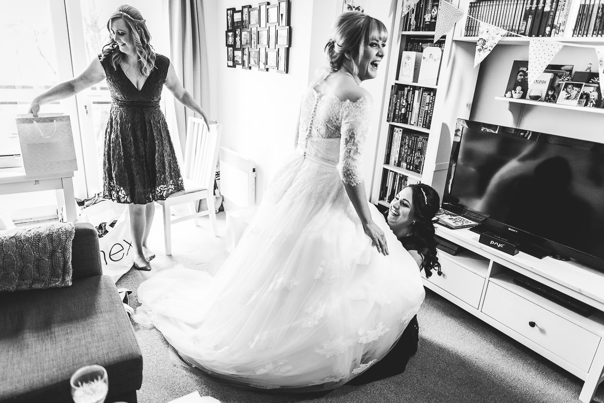 Bride having garter adjusted