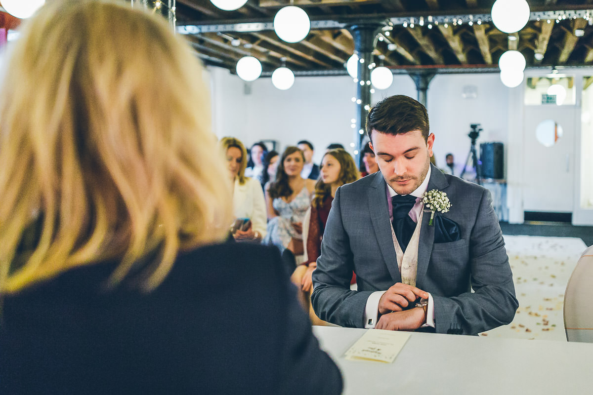 Groom nervously checking watch before wedding