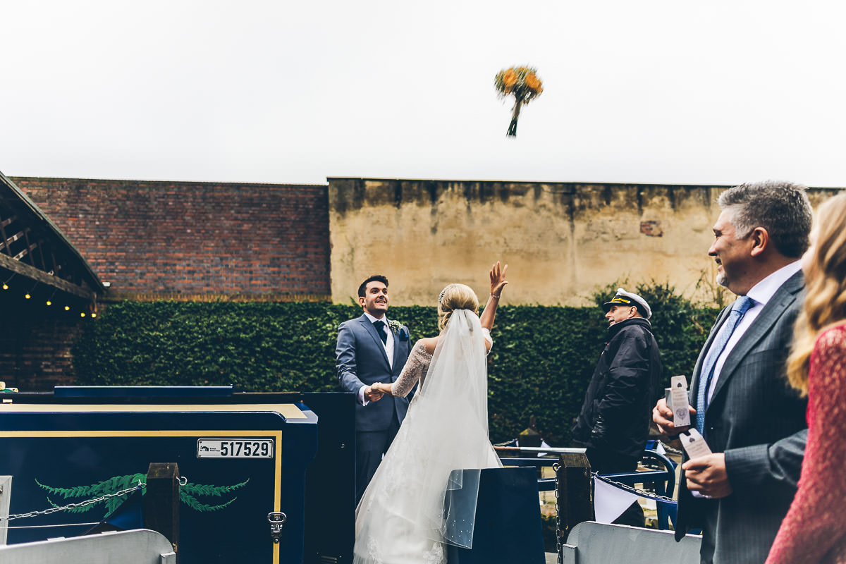 Bride throwing bouquet from a narrow boat